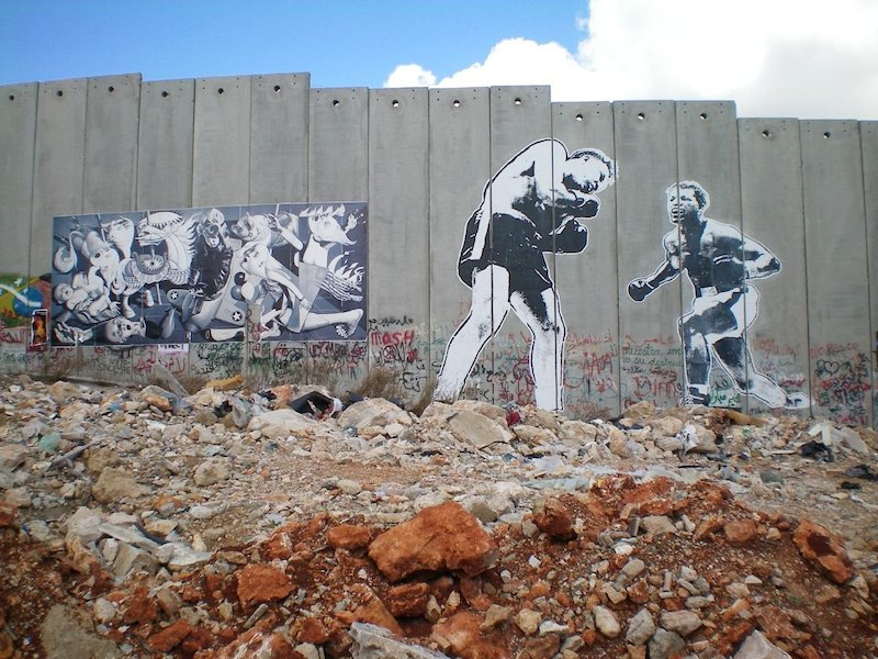 Work put up by Ron English and Faile on the separation wall in the West Bank as part of Banksy's Santa's Ghetto project in Bethlehem. Photo by eddiedangerous.
