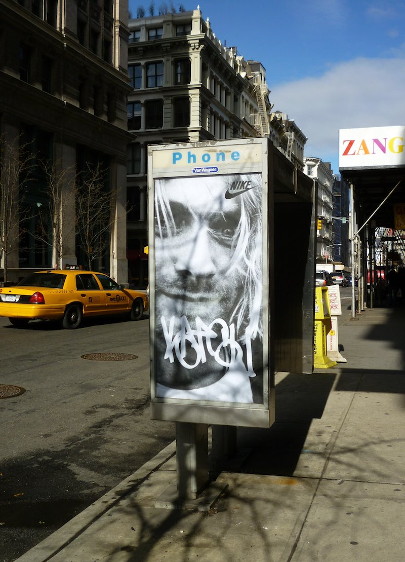 A phone booth ad takeover by KATSU featuring Kurt Cobain and the Nike logo. Photo by carnagenyc.