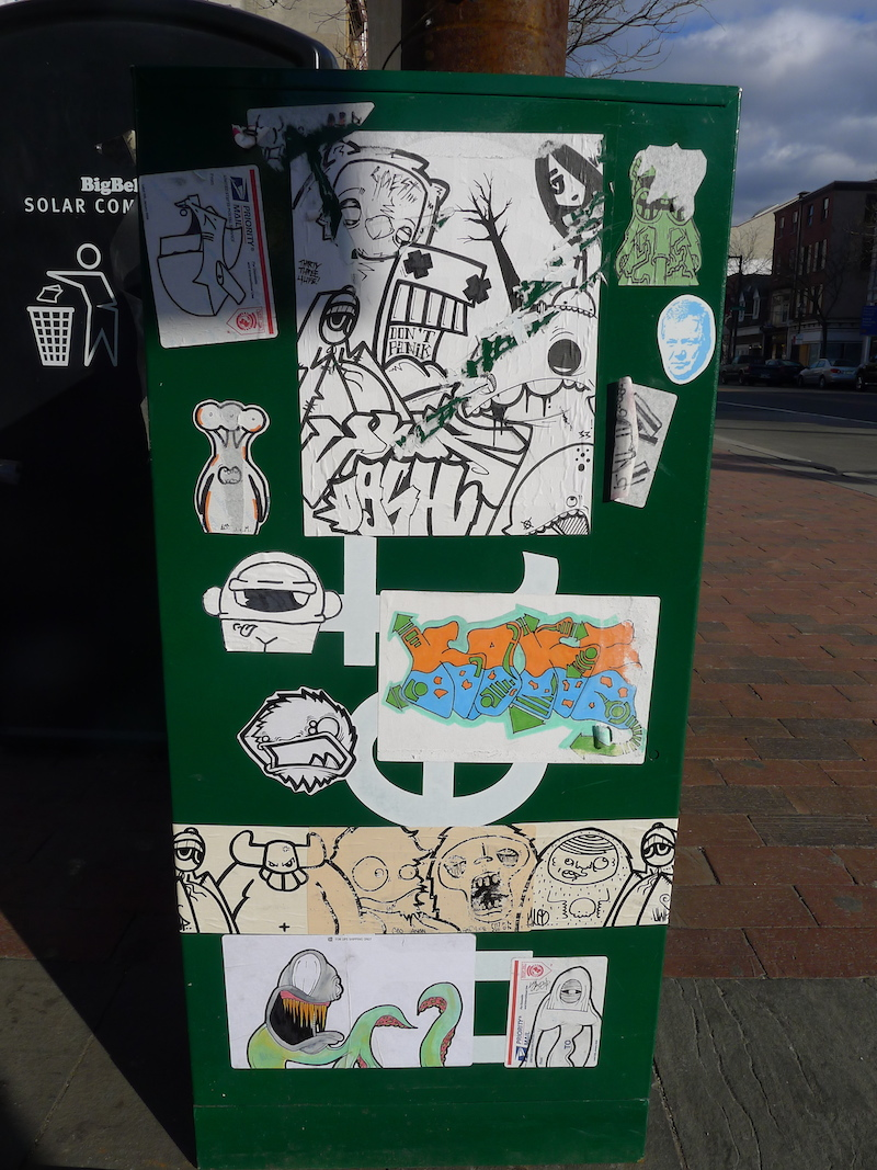 Stickers by various artists on a newsbin in Philadelphia. Photo by RJ Rushmore.